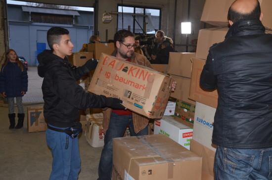 Beim Verladen von Hilfsgütern für Flüchtlinge.