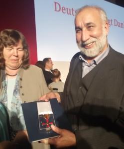 DAF-Gründer Aga Zia Farsin hält das Bundesverdientskreuz in den Händen.